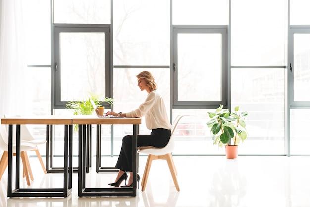 ラップトップを使用してオフィスに座っている幸せな若いビジネス女性
