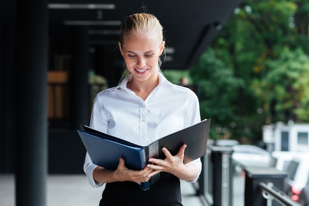 Happy young business woman standing and holding folders outside