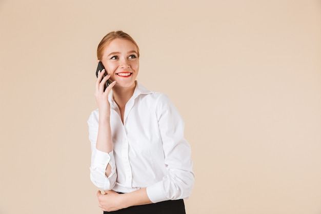 Happy young business woman talking by mobile phone.