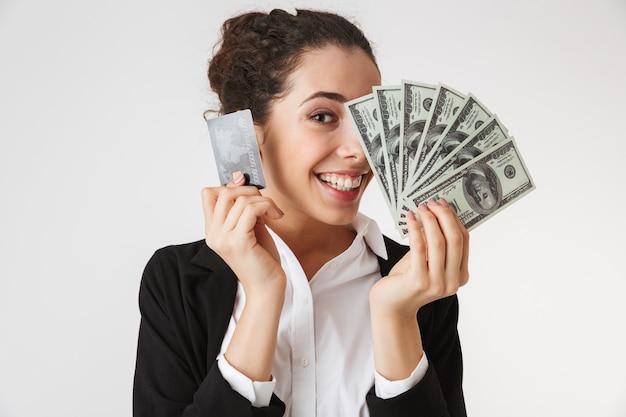 Счастливая молодая деловая женщина с кредитной картой и деньгами
