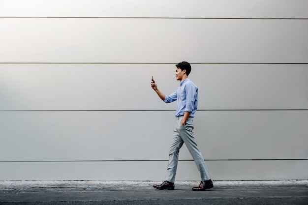 Happy young businessman in casual wear using mobile phone while walking by the urban building wall. lifestyle of modern people.