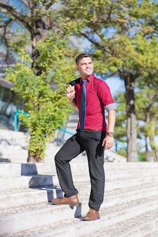 Happy young businessman going upstairs outdoors