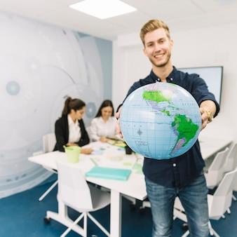 Счастливый молодой бизнесмен, проведение земного шара в офисе