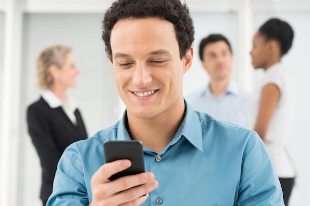Счастливый молодой бизнесмен, глядя на мобильный телефон в офисе