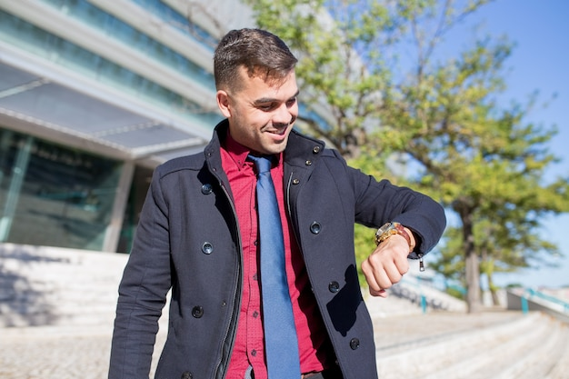 Happy young businessman looking at watch outdoors