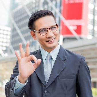 Happy young businessman make okay gesture. okay symbol.