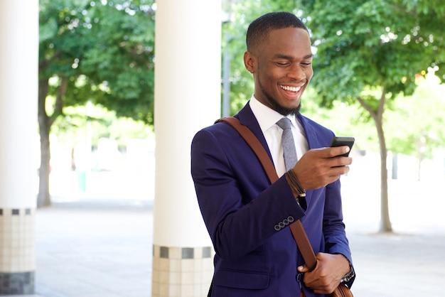 그의 휴대 전화에서 문자 메시지를 읽고 행복 한 젊은 사업가