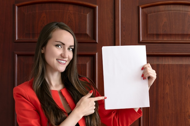 Happy young businessman in red suit, holding blank white sheet for text on background of office wooden doors.