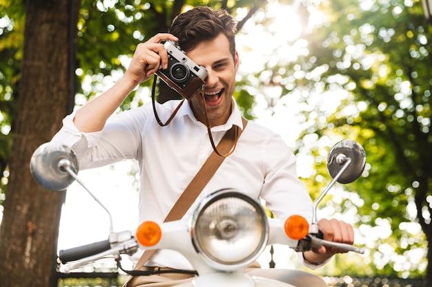 フォトカメラで写真を撮って、屋外でバイクに乗って幸せな青年実業家