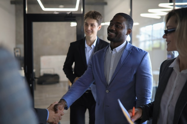 Happy young businessman shaking hands with his business partner.