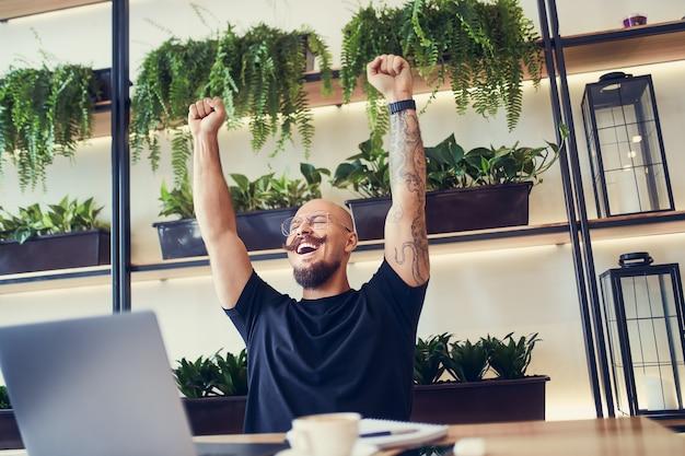 행복한 젊은 사업가가 노트북에 앉아 좋은 뉴스 온라인 행운의 우승자가 손을 들어 흥분을 일으키고 있습니다.