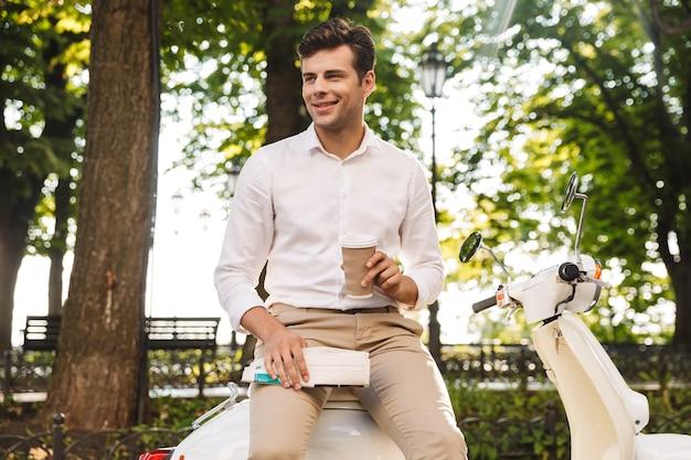 Счастливый молодой бизнесмен сидит на мотоцикле на открытом воздухе, читает газету, пьет кофе