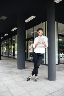 ビジネスセンターの近くに立って、タブレットを使用して幸せな青年実業家