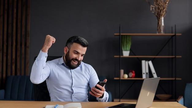Счастливый молодой бизнесмен удивлен хорошими новостями и делает жест «да», глядя на смартфон, сидя в офисе.