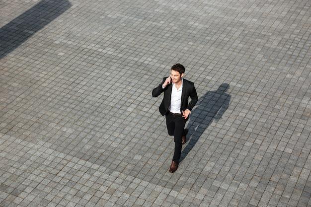 Giovane uomo d'affari felice che cammina all'aperto