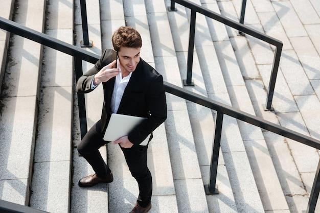 Giovane uomo d'affari felice che cammina all'aperto Foto Gratuite