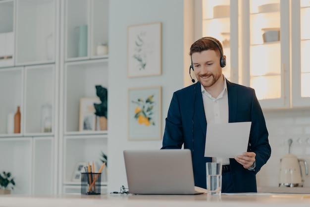 Счастливый молодой бизнесмен носить костюм и гарнитуру, работая удаленно из дома, используя видеосвязь с коллегами на ноутбуке, держа документ в руке. концепция удаленной работы