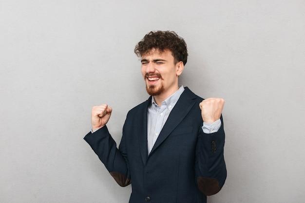 Счастливый молодой бизнесмен в костюме, стоящем изолированным над серым, празднует успех