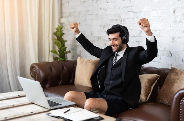 Счастливый молодой бизнесмен работает из дома, глядя на ноутбук, взволнован, удачлив и успешен и поднимает руку, празднуя результат победы.