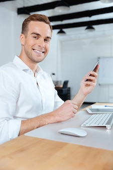 Счастливый молодой бизнесмен, работающий и использующий смартфон в офисе