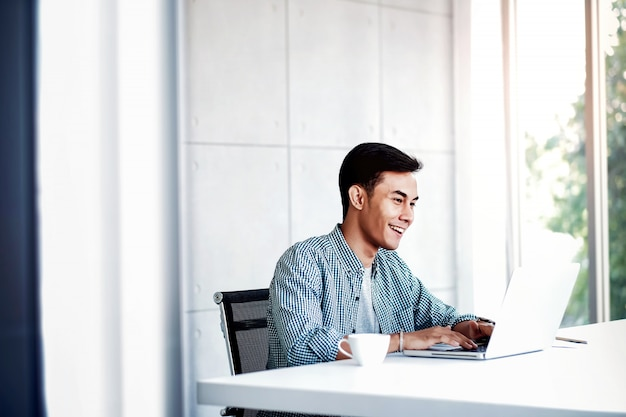 Happy young businessman working on computer laptop in office.