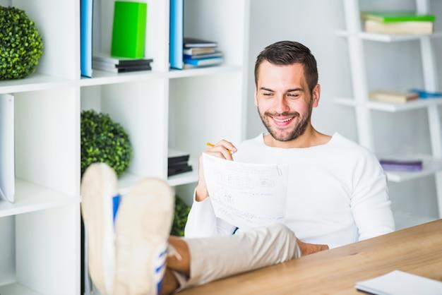 Счастливый молодой бизнесмен, работающих на документ на рабочем месте