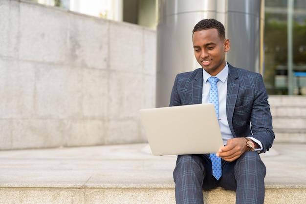 야외 계단에 앉아있는 동안 노트북으로 작업하는 행복 젊은 사업가