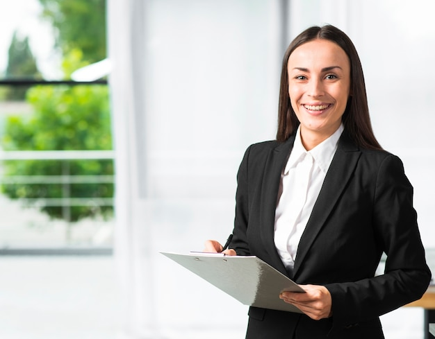 Happy young businesswoman holding clipboard and pen looking at camera