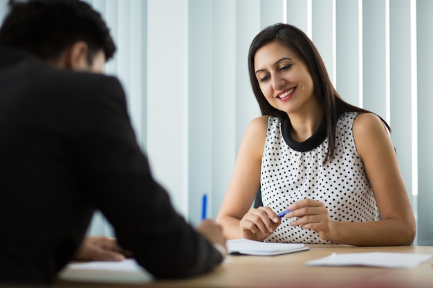 Happy young businesswoman looking at partner signing contract