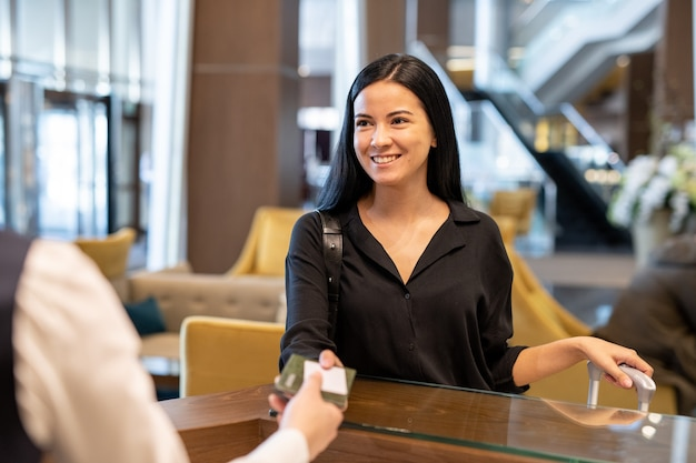 Счастливый молодой предприниматель или женщина-путешественница с багажом, передавая ее документы администратору отеля через стойку перед регистрацией