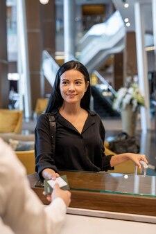 Счастливый молодой предприниматель или женщина-путешественница с багажом, стоящим у стойки регистрации и передавая ее документы портье