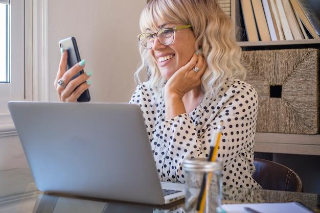机の上にラップトップを持ってオフィスで携帯電話を使用して良いニュースを受け取る幸せな若い実業家。オフィスや自宅で電話を使用してソーシャルメディアコンテンツを見ている女性。自宅で働く女性