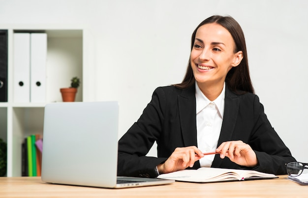 Happy young businesswoman sitting behind the desk with book; pen and laptop