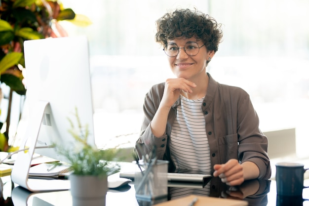 Happy young businesswoman in smart casual watching online video on computer screen while working in office