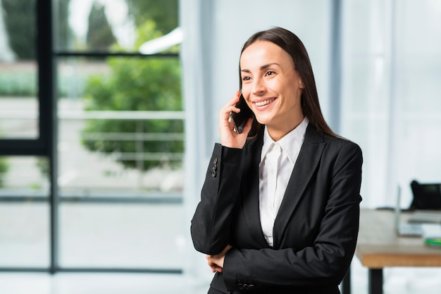 Happy young businesswoman standing in the office talking on cellphone