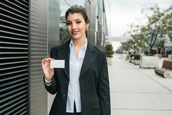 Happy young businesswoman standing outside the office building showing her business card