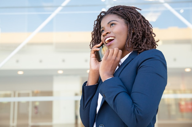 Happy young businesswoman talking by smartphone