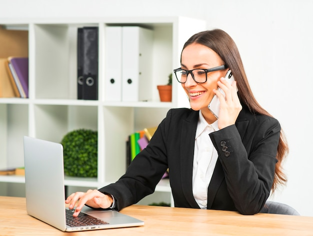 Happy young businesswoman talking on smartphone typing over laptop