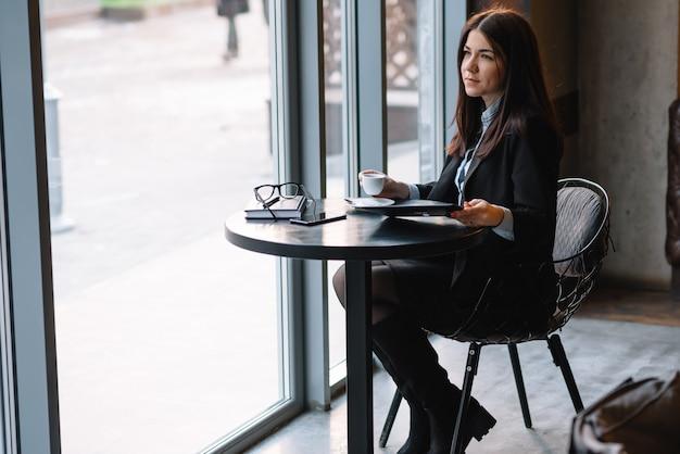 Счастливый молодой предприниматель с помощью планшетного компьютера в кафе