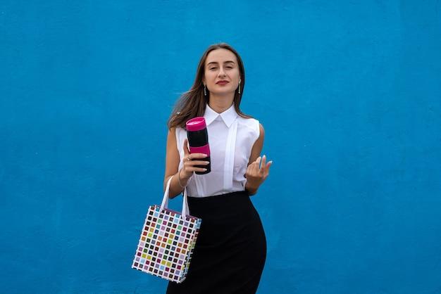 ショッピングバッグと青い背景で隔離のコーヒーのカップを保持している幸せな若い実業家。コピースペース