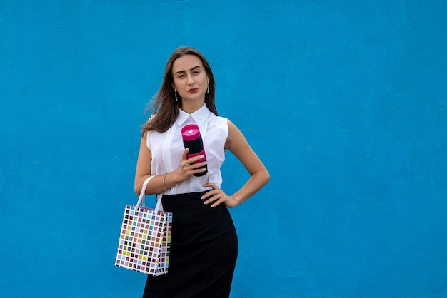 Happy young businesswoman with  shopping bags and holding cup of coffee isolated on blue background. copy space