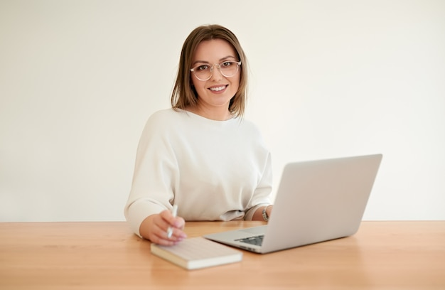 Happy young businesswoman working on netbook in office