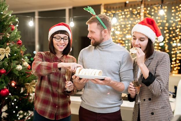 Счастливые молодые бизнесмены в шапках санта-клауса, наслаждаясь десертом и шампанским на рождественской вечеринке в офисе