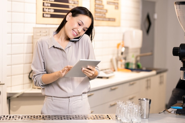 Happy young busy waitress of cafe or restaurant talking to one of clients on the phone while scrolling through online orders in touchpad