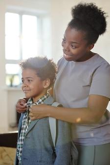 Счастливая молодая осторожная женщина африканской национальности застегивает рубашку своего маленького сына с рюкзаком, провожая его в школу утром