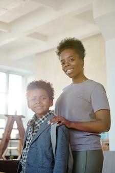 Счастливая молодая заботливая мать держит руки на плечах своего маленького сына с рюкзаком, провожая его в школу перед камерой