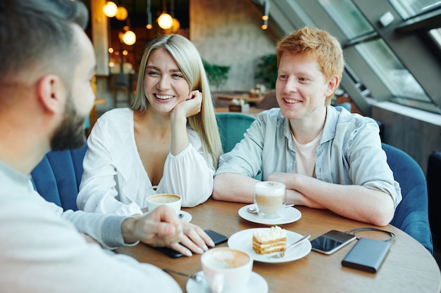 Happy young casual couple chatting to their friend by cup of cappuccino and dessert while sitting by table in cafe