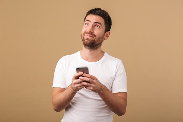 Счастливый молодой случайный человек, держащий мобильный телефон изолирован