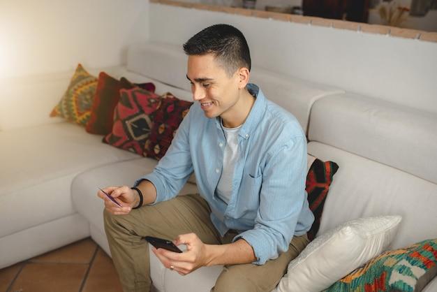 スマートフォンとクレジットカードを保持しているソファに座って幸せな若いカジュアルな男。新規購入のための笑顔。
