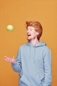 Счастливый молодой случайный мужчина бросает зеленое яблоко перед собой, развлекаясь перед камерой над желтой стеной в изоляции